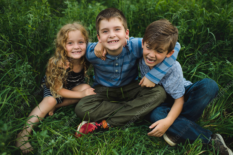 Brothers and sister enjoying outdoors on green grassy field