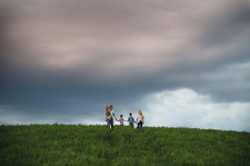 Family of five enjoying outdoors on green grassy field