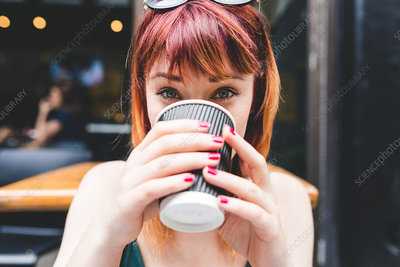 Portrait of woman drinking coffee at sidewalk cafe table