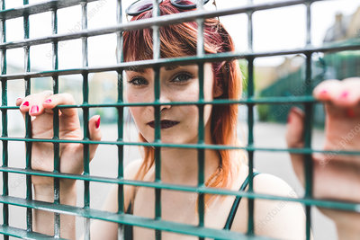 Portrait of woman with dip dyed hair behind wire fence
