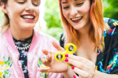 Two retro styled women playing with fidget spinner in park