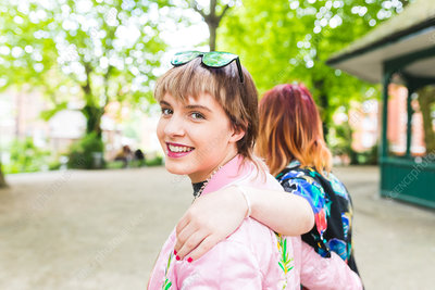 Portrait of two retro styled young women strolling in park