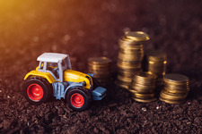 Toy tractor with stacked coins, conceptual image