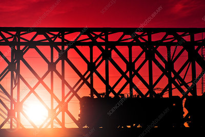 Train crossing bridge at sunset