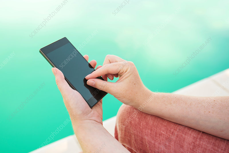 Using mobile phone by the swimming pool