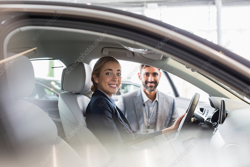 Portrait woman and car salesman sitting in car