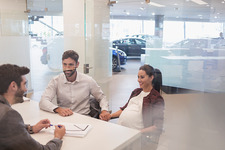 Car salesman talking to pregnant couple in office