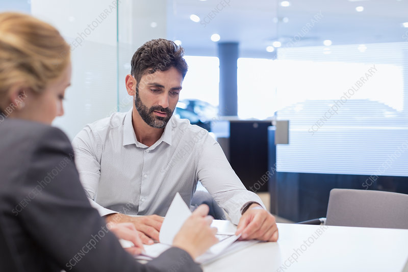 Car saleswoman explaining paperwork to customer
