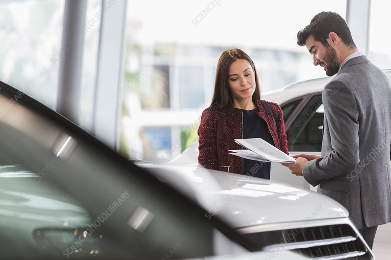 Car saleswoman showing brochure to customer