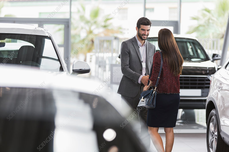 Car salesman greeting, shaking hands with customer