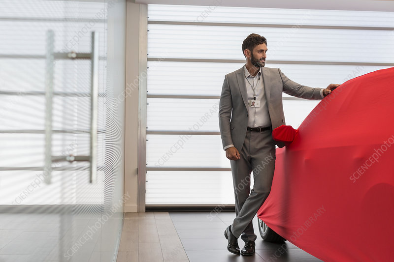Car salesman standing at covered car in showroom