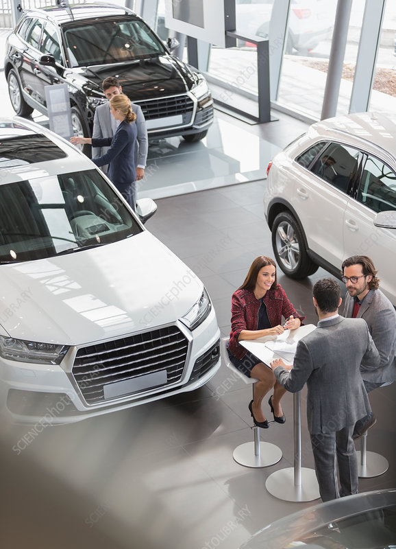 Car sales people meeting at table in showroom