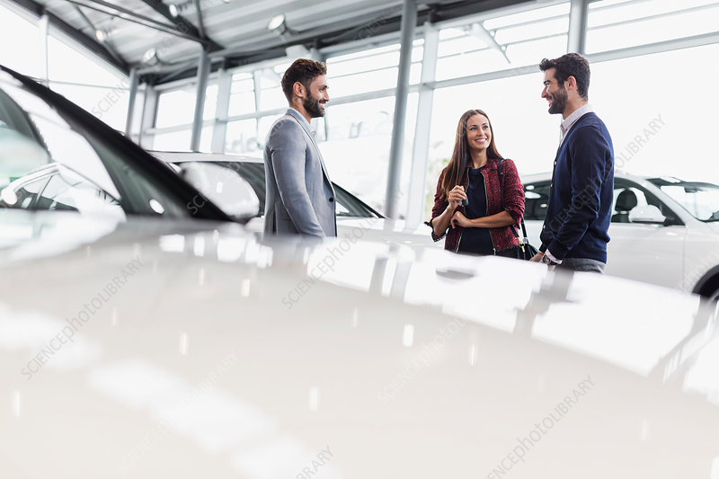Car salesman talking to couple customers