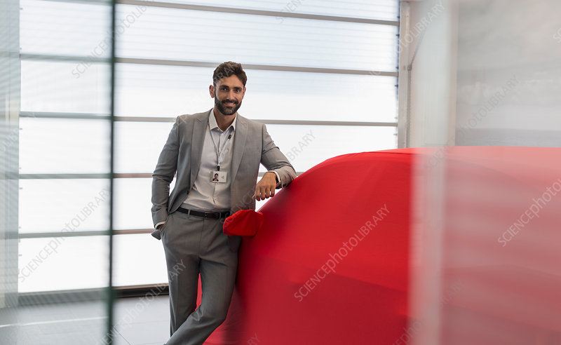 Portrait car salesman leaning on covered car