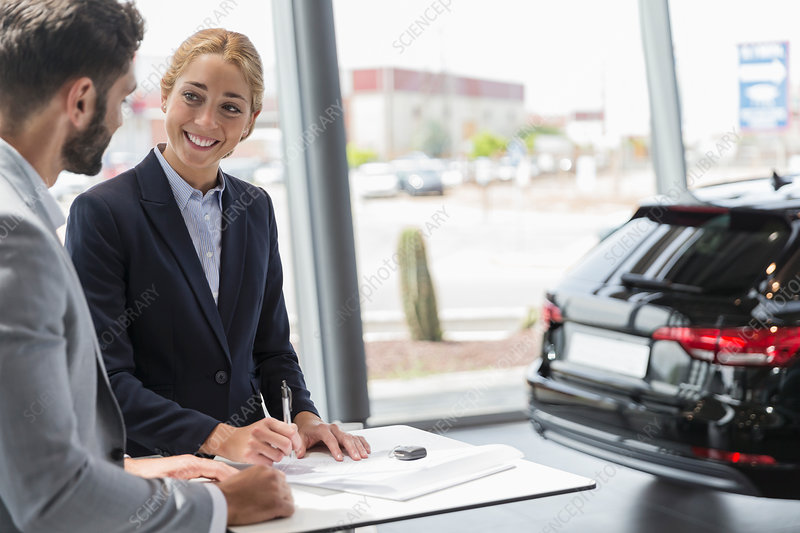 Car saleswoman and customer signing contract