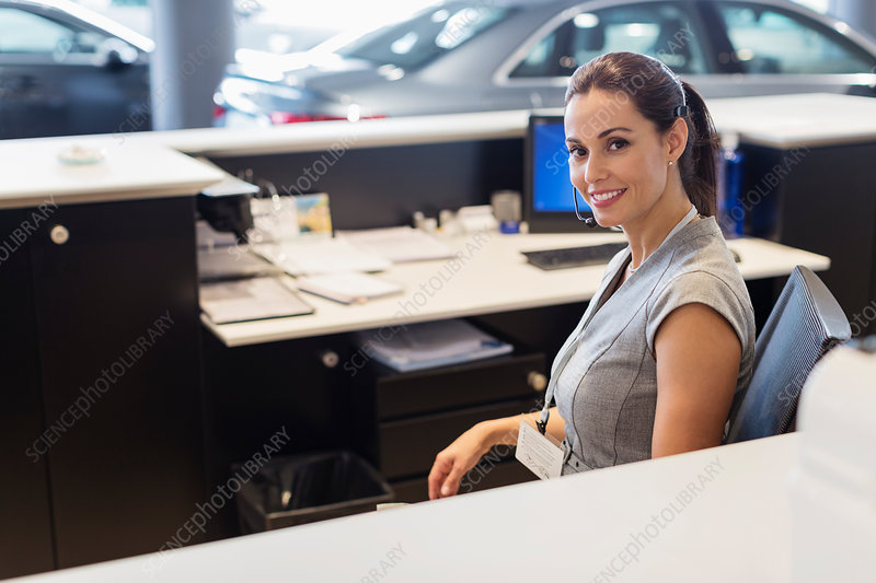 Portrait receptionist working at desk in showroom