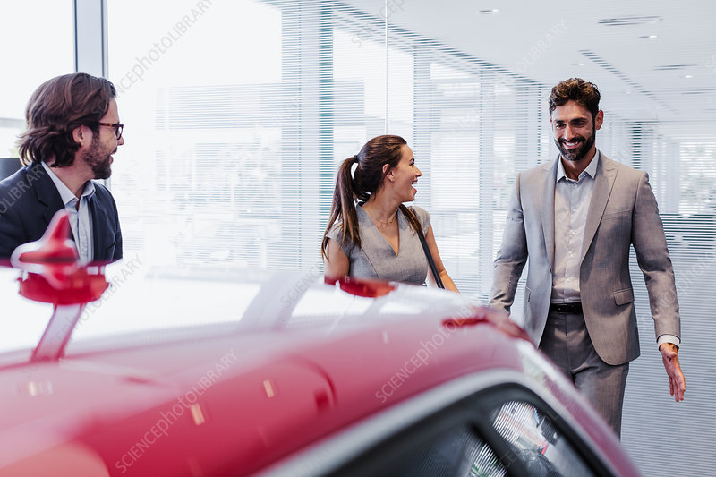 Car salesman and couple customers looking at car