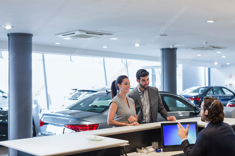 Couple customers talking to receptionist at desk