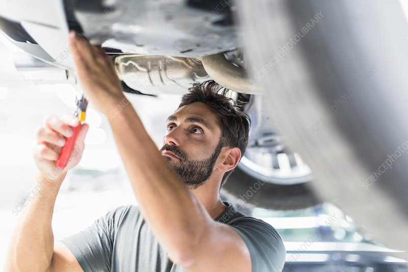 Focused mechanic working under car