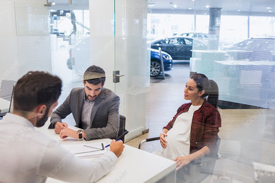 Car salesman showing paperwork to pregnant couple