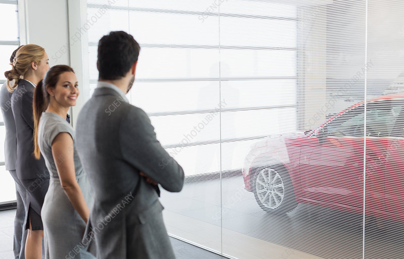 Car sales people looking at new, red car