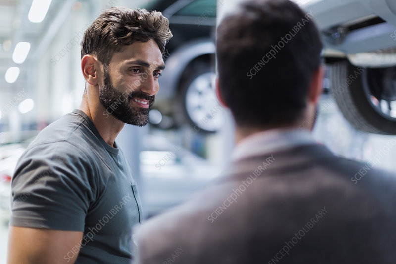 Smiling auto mechanic talking to customer
