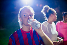 Young soccer player drinking from water bottle