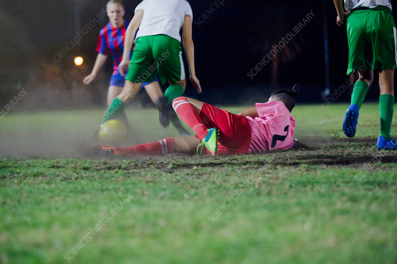 Soccer player falling, kicking the ball