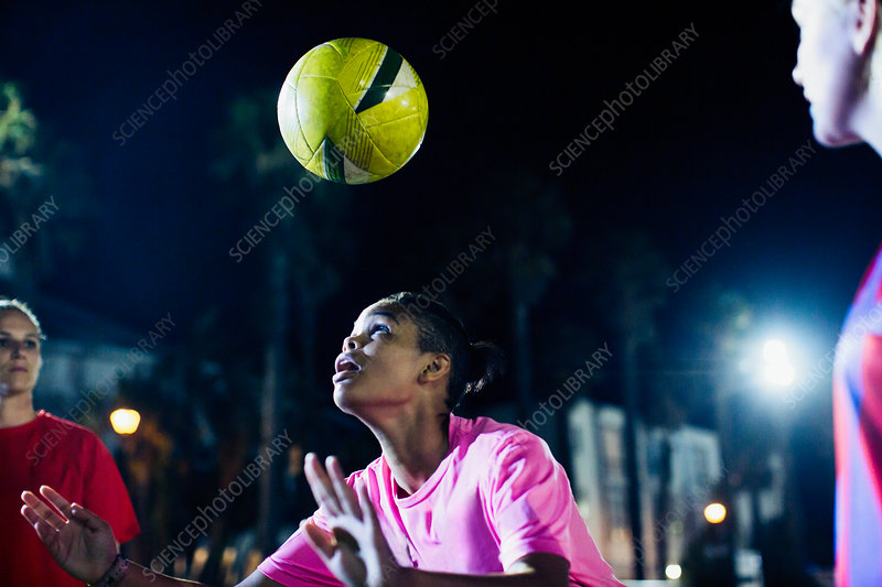 Young soccer player heading the ball at night