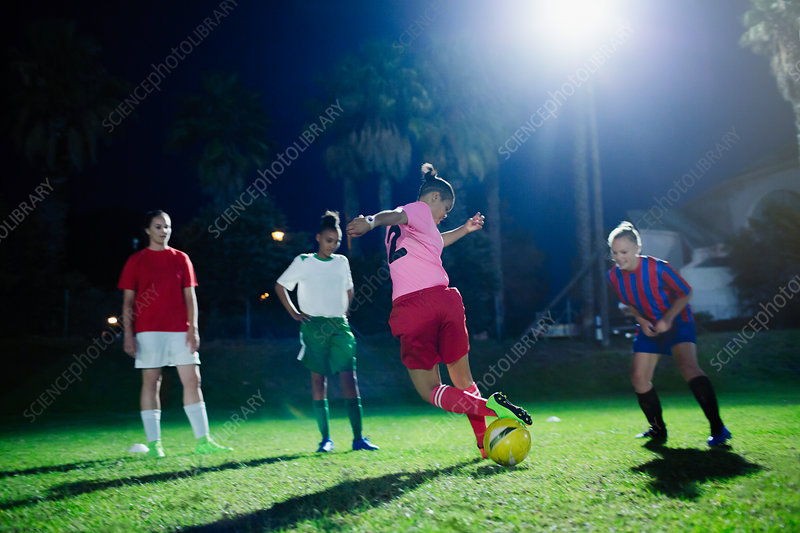 Young soccer players practicing at night