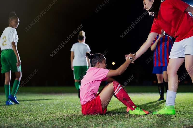 Young soccer player helping fallen teammate get up