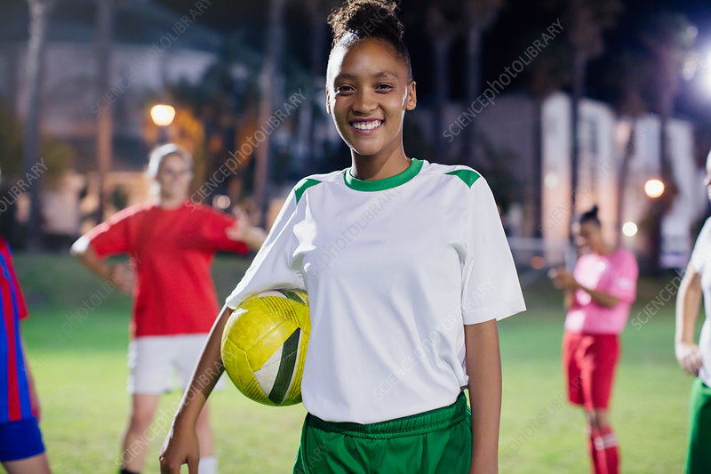 Portrait young soccer player with ball at night