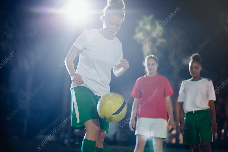 Soccer player practicing, kneeing the ball