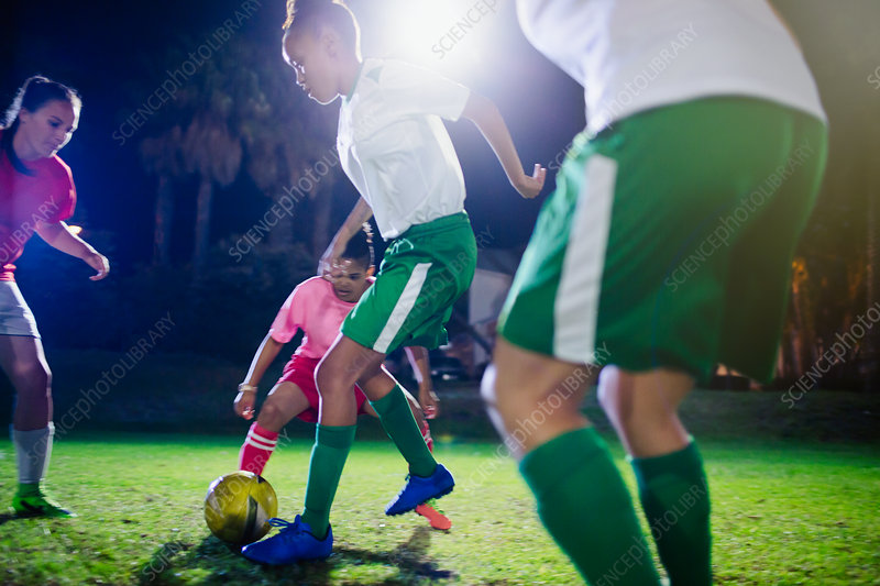 Young soccer players playing at night