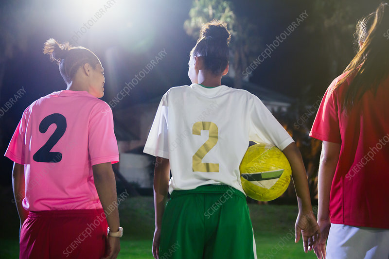 Young soccer players with ball talking at night