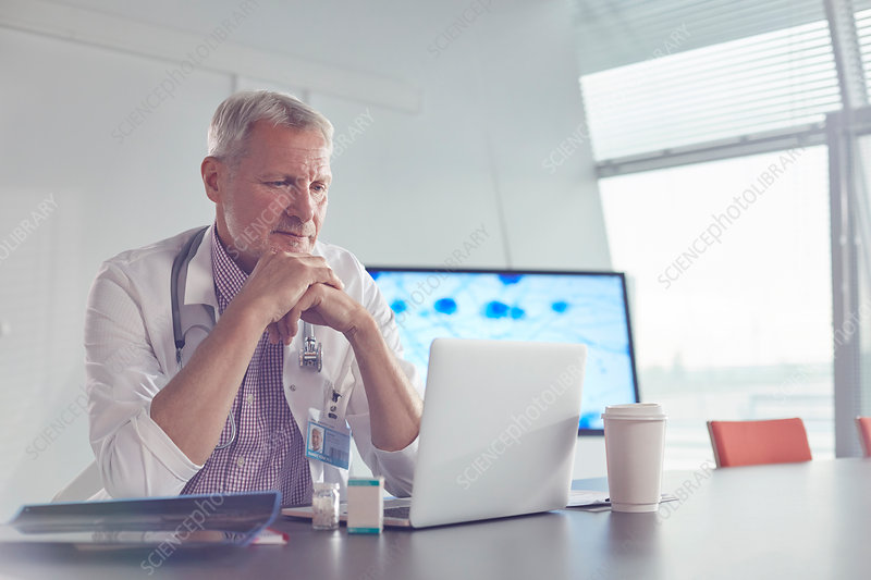 Medical scientist working at laptop