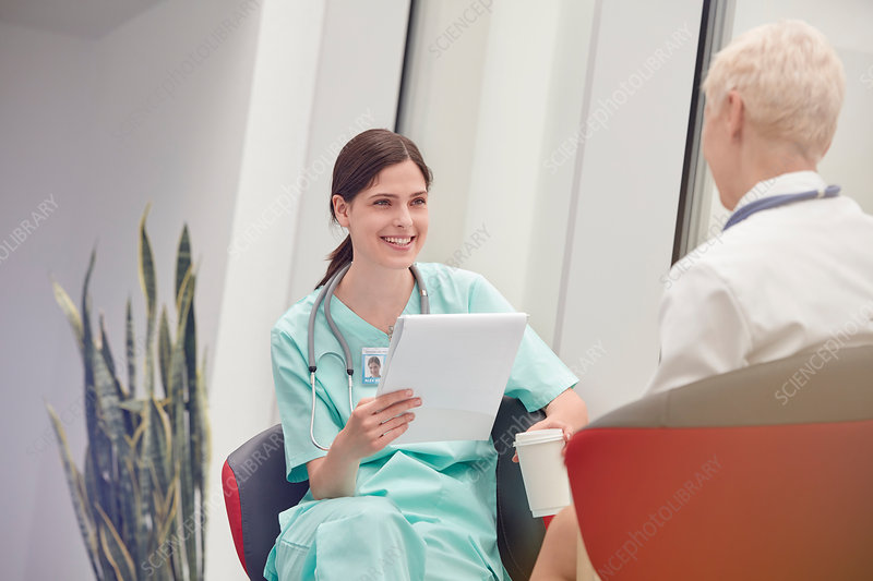 Smiling nurse talking to doctor in hospital