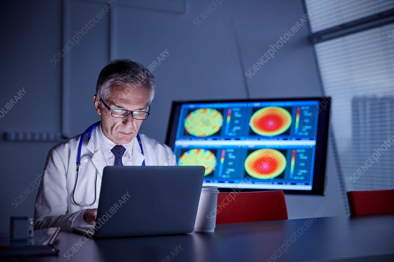 Focused surgeon working at laptop in hospital
