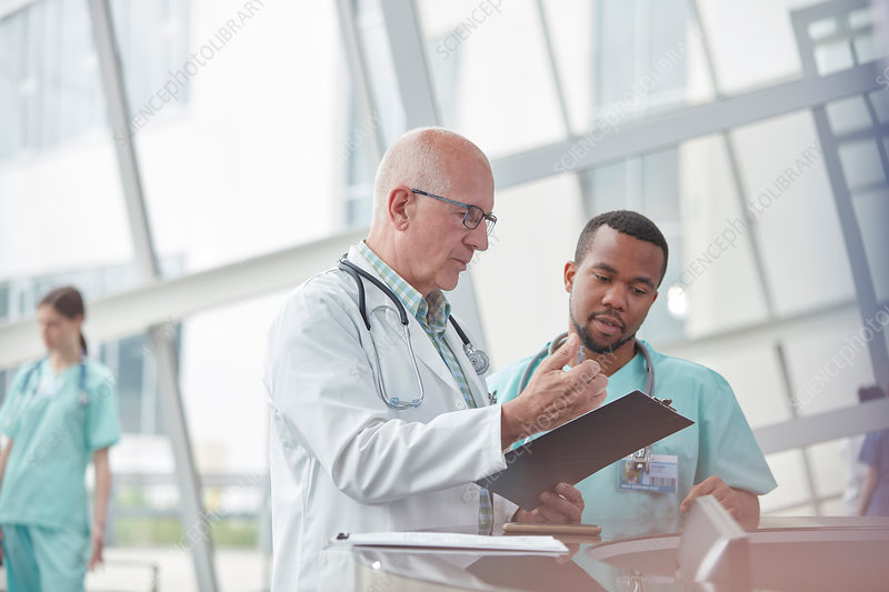 Male doctor and nurse talking in hospital lobby
