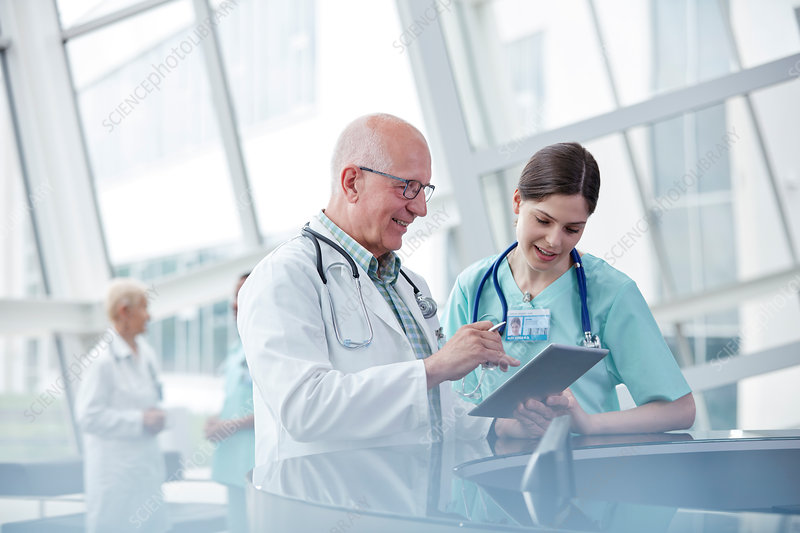 Doctor and nurse with digital tablet talking