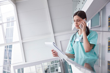 Female nurse talking on cell phone in hospital