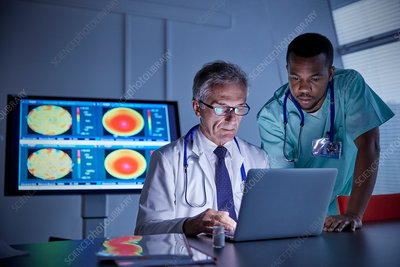 Male surgeon and doctor working at laptop