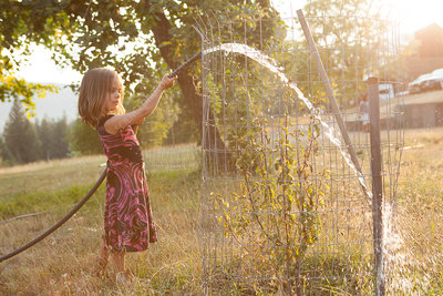 Girl in dress watering tree with hose