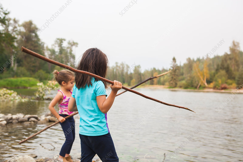 Girls fishing with sticks at lake