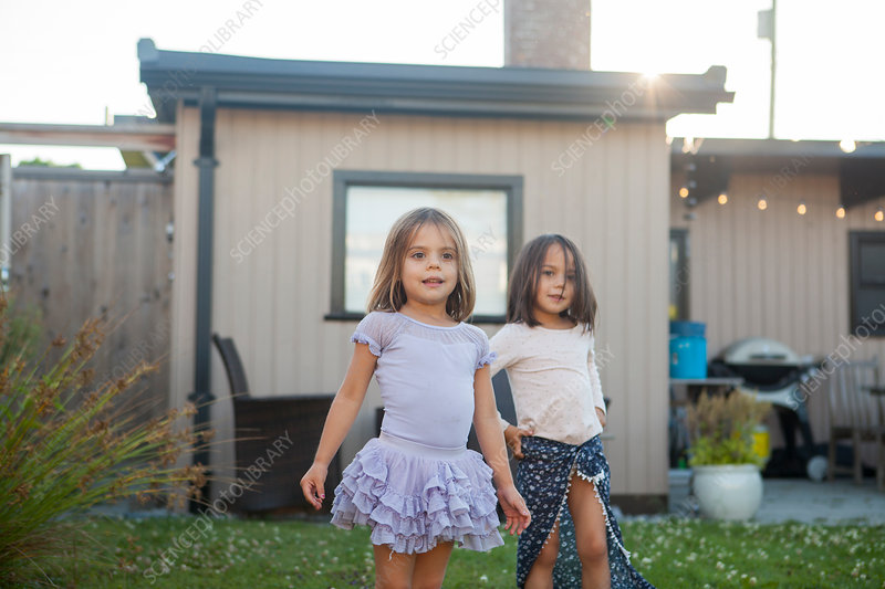 Portrait girl sisters in skirts in yard