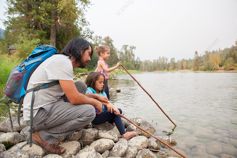 Father and daughters fishing at lakeside