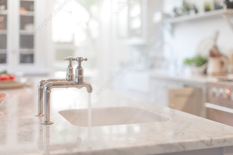 Water running from faucet in kitchen sink