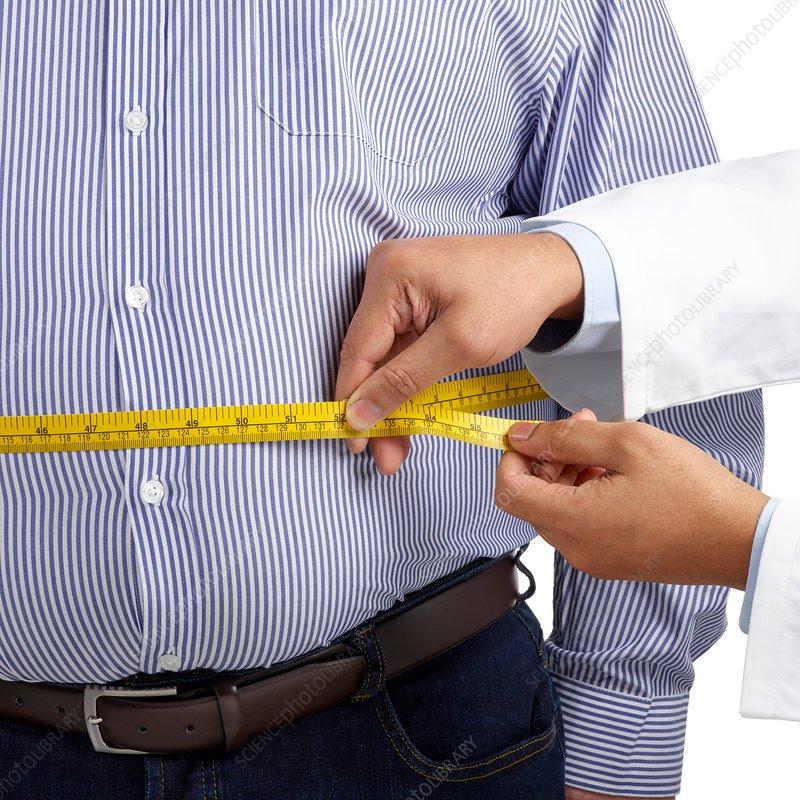 Doctor measuring man's waist