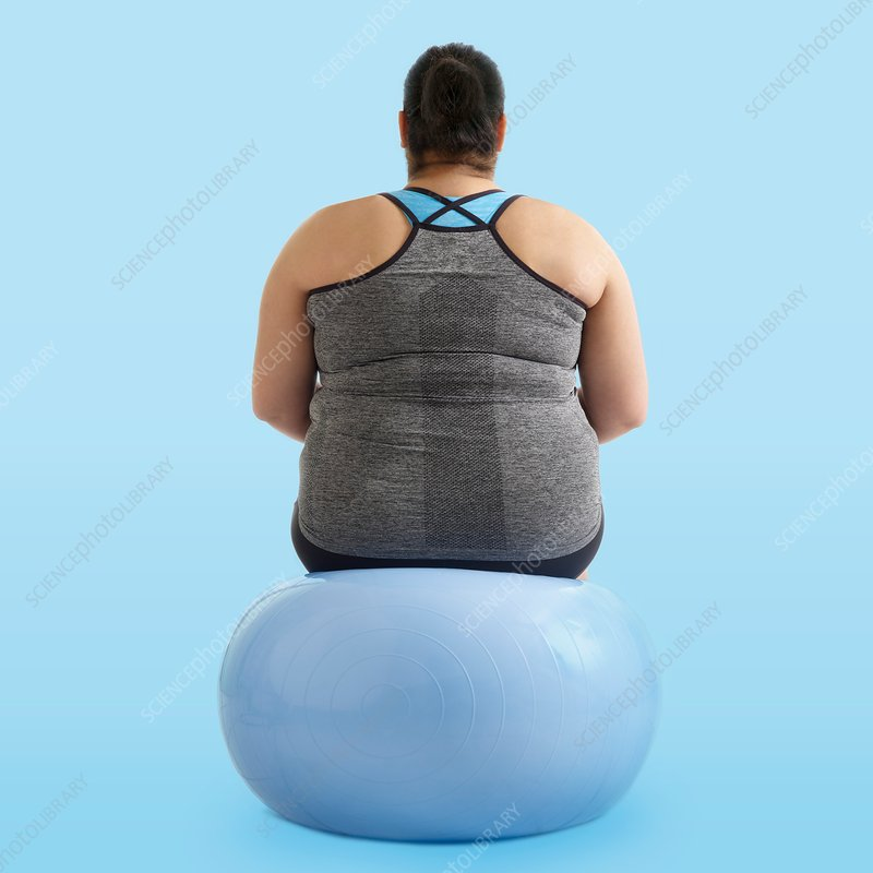 Overweight woman sitting on an exercise ball