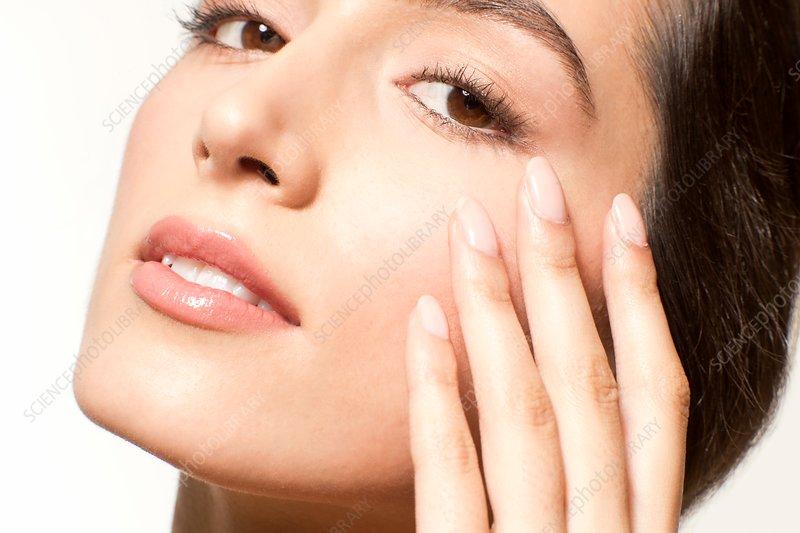 Woman touching skin near eye